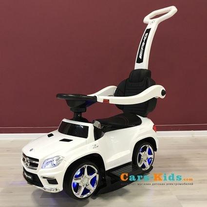 Толокар Mercedes-Benz GL63 A888AA-H с ручкой и качалкой белый (музыка, свет фар и колес, колеса резина, сиденье кожа)